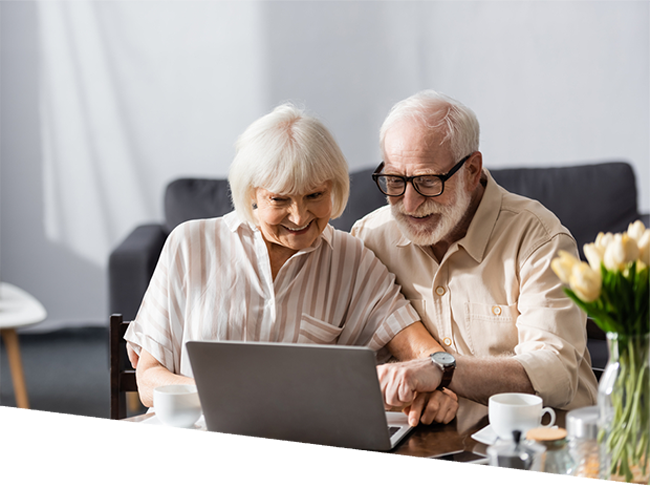 Smiling elderly couple using laptop near coffee cups on table